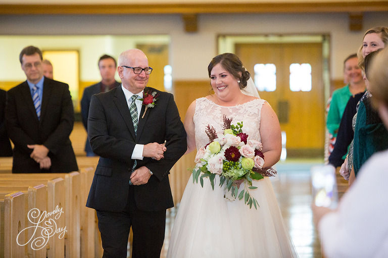 Dad crying as he walks his daughter, the bride down the aisle in a church.