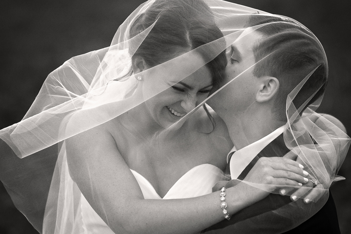 grooms whispers something funny to bride during a wedding in Buffalo NY