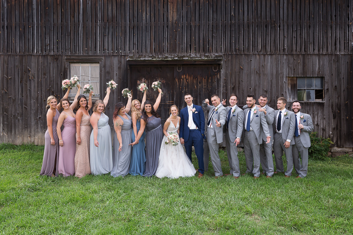 Barn wedding party wearing blush and blue while guys wear grey and navy suits